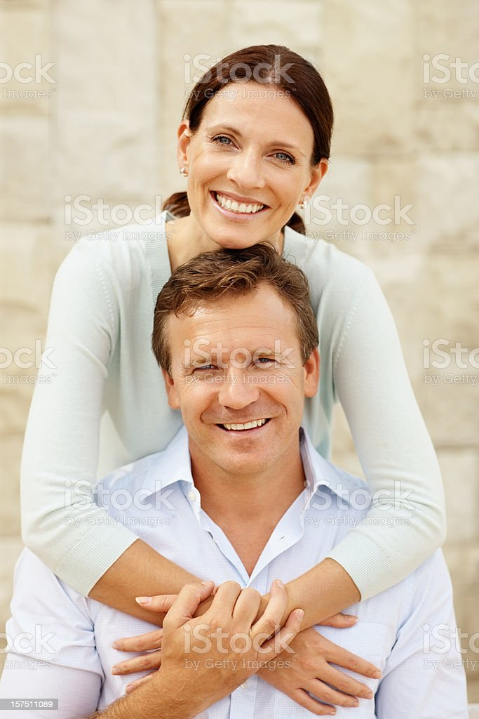 Happy wife embracing her husband from behind royalty-free stock photo