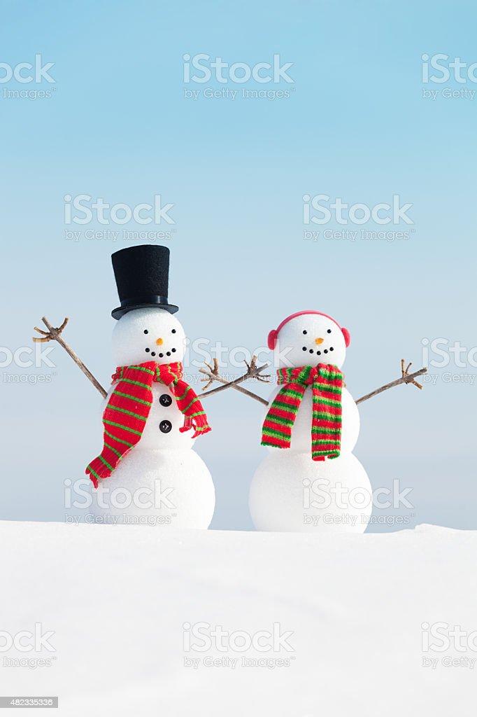 Happy Winter Snowman Christmas Couple in Snow Scene stock photo
