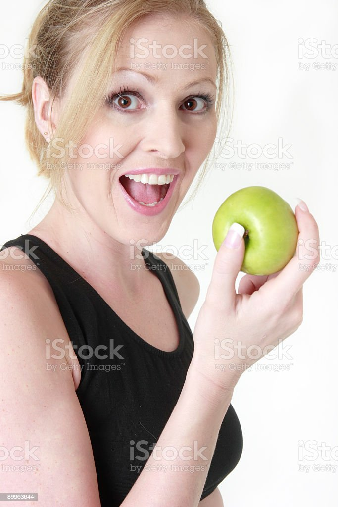 Happy woman about to eat an apple royalty-free stock photo