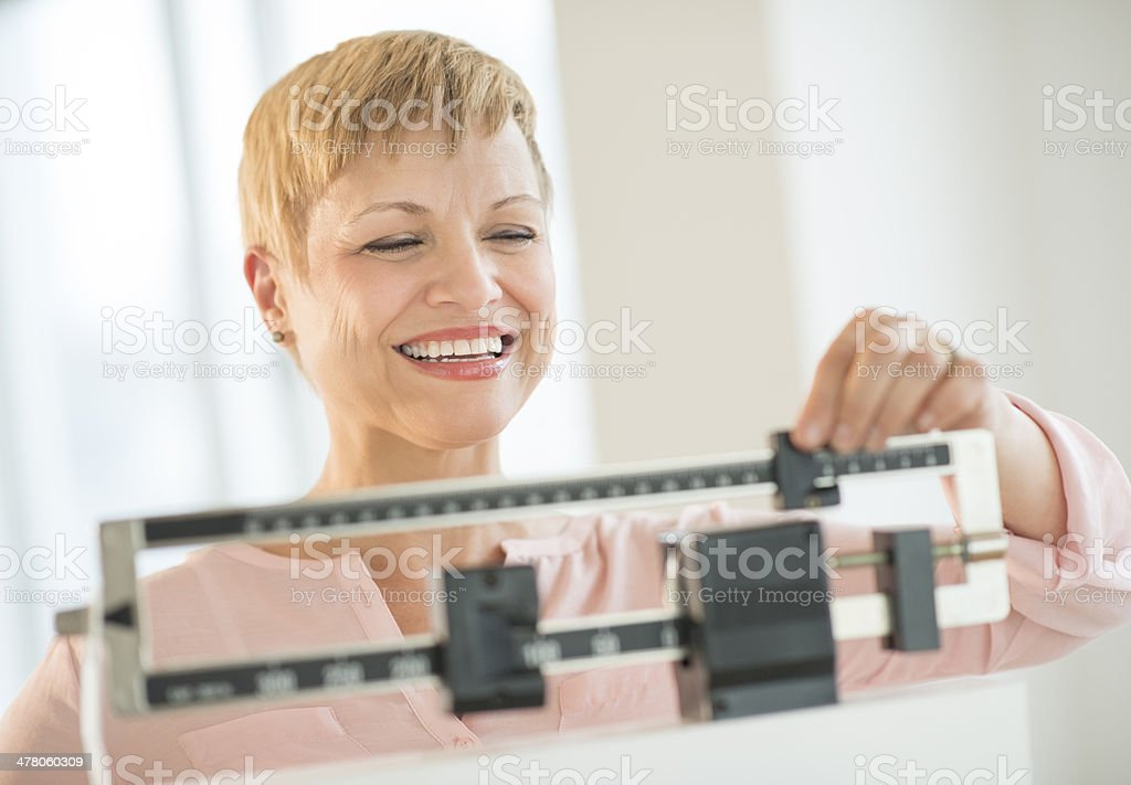 Happy Woman Adjusting Balance Weight Scale stock photo