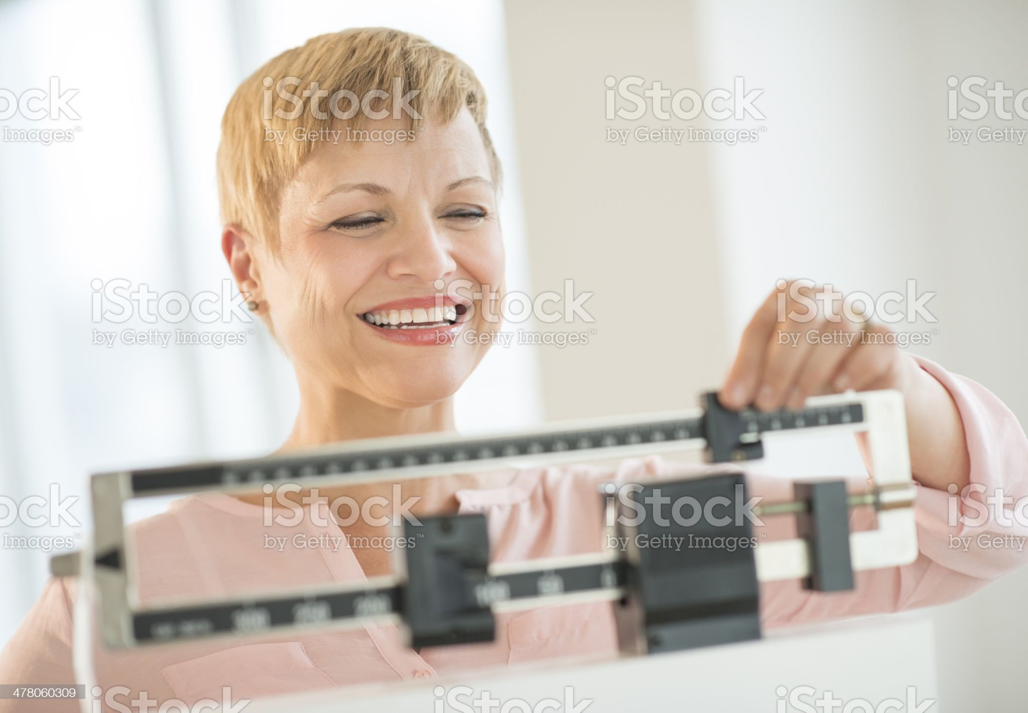 Happy Woman Adjusting Balance Weight Scale royalty-free stock photo