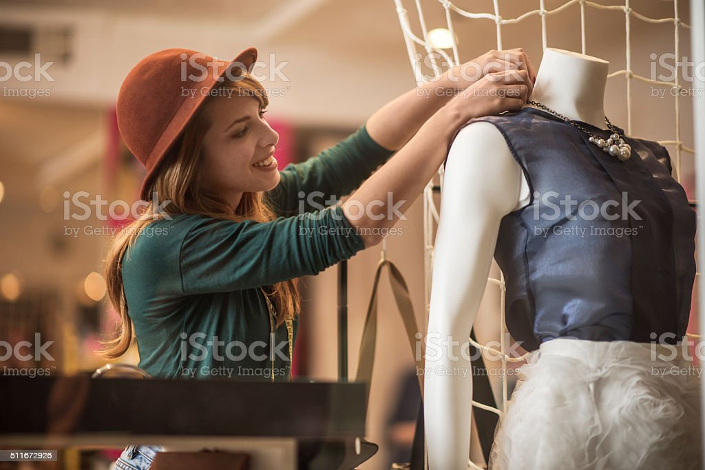 Happy woman adjusting blouse on a mannequin in a store. stock photo