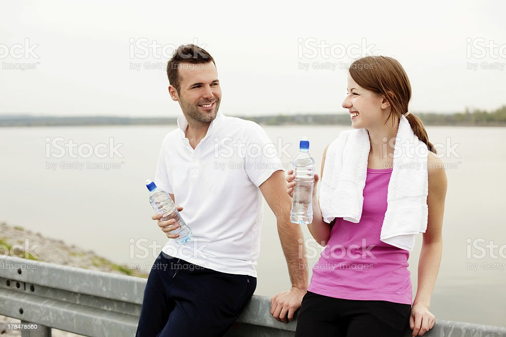Happy woman and man talking,  drinking water after exercise stock photo