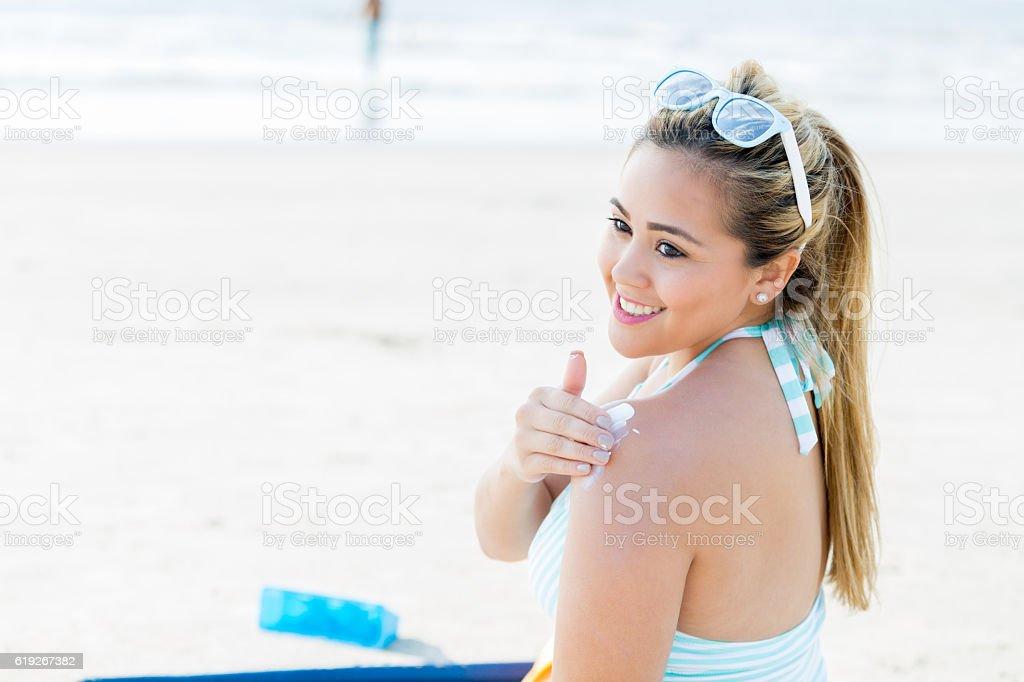 Happy woman applies sunscreen on the beach stock photo