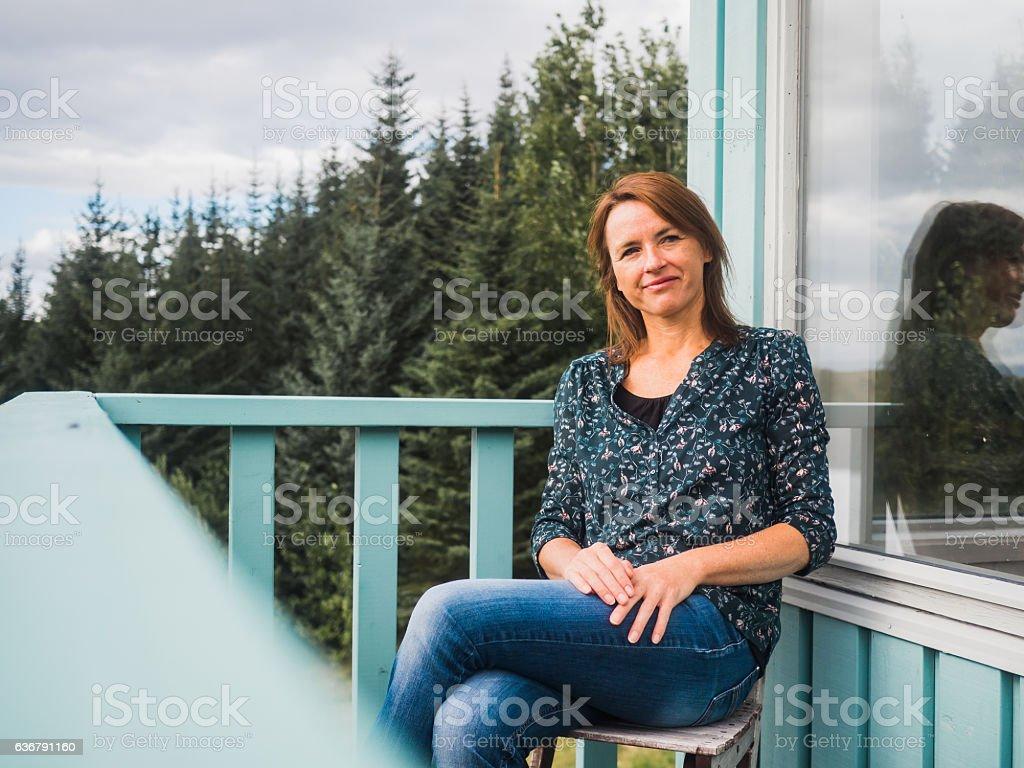Happy woman at a balcony stock photo
