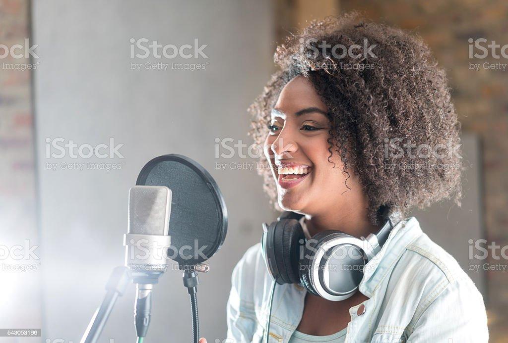 Happy woman at a recording studio stock photo