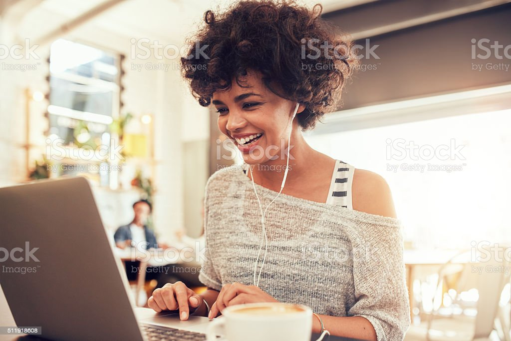 Happy woman at cafe using laptop stock photo