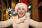 happy woman at Christmas in Florence, Italy taking selfie