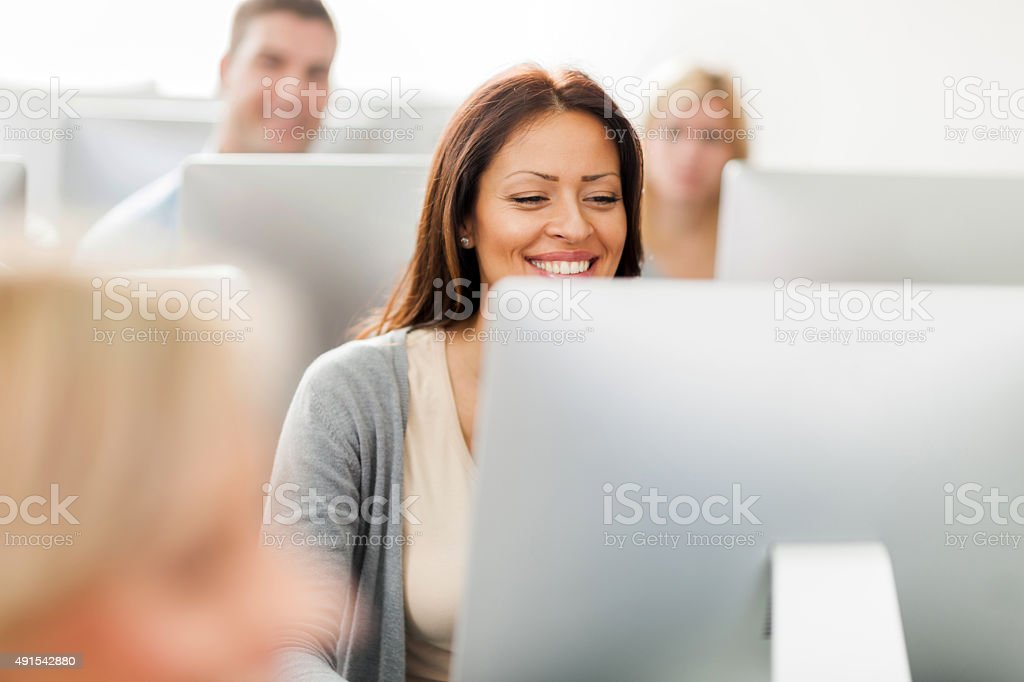 Happy woman at computer class. stock photo