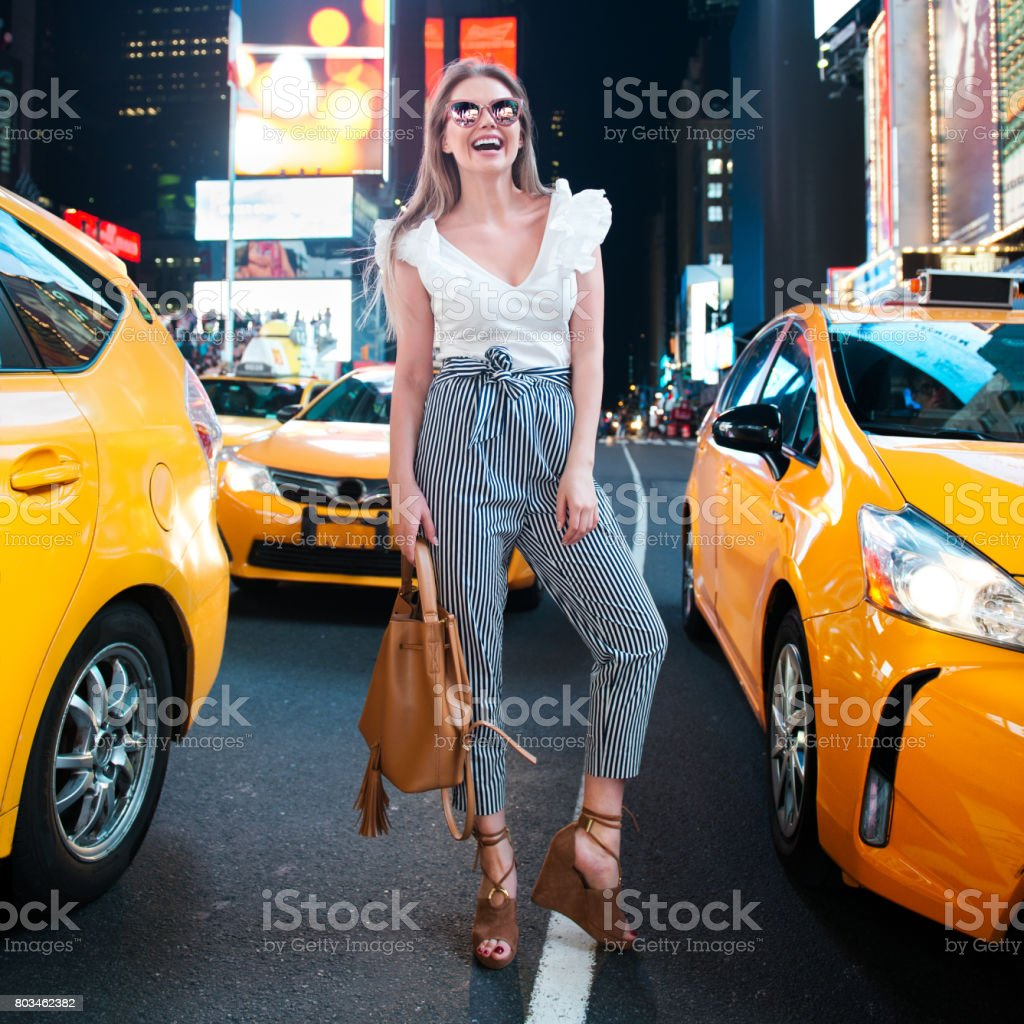 Happy woman at night New York City Times Square street stock photo