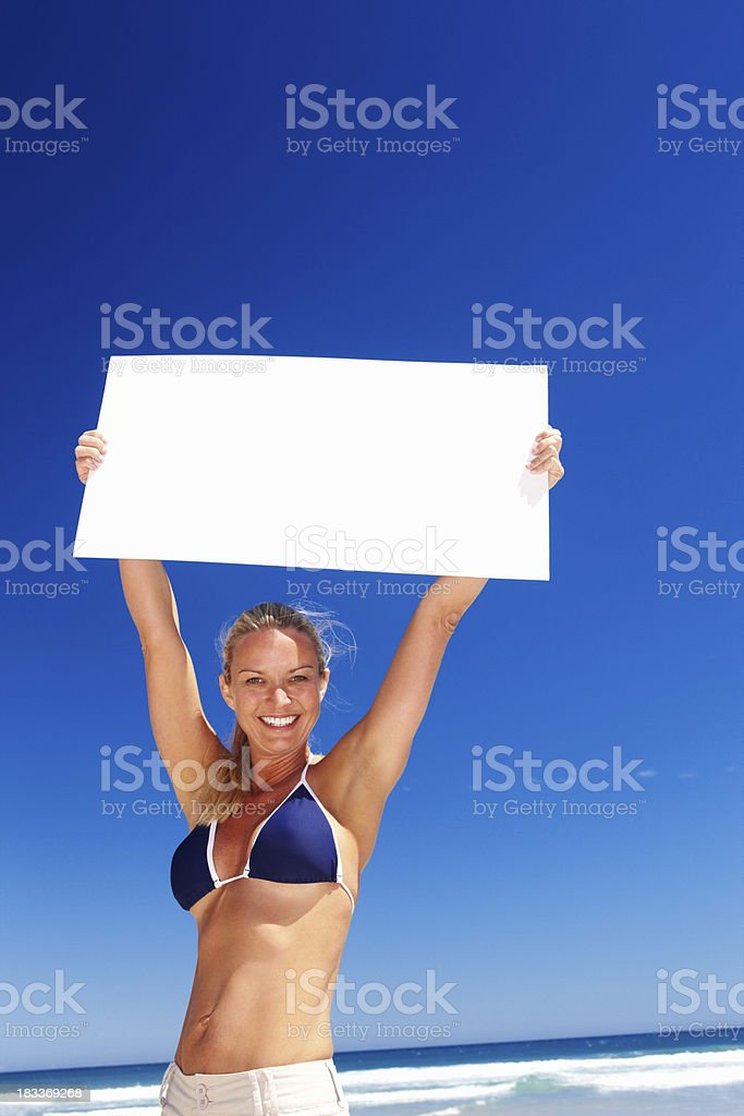 Happy woman at the beach holding sign above her head royalty-free stock photo