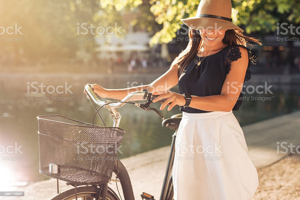 Happy woman at the park with a bike stock photo