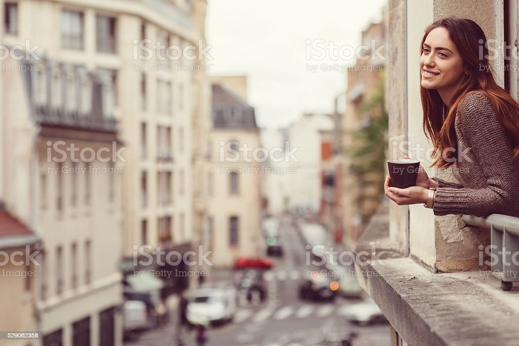 Happy woman at the window with a cup of coffee stock photo
