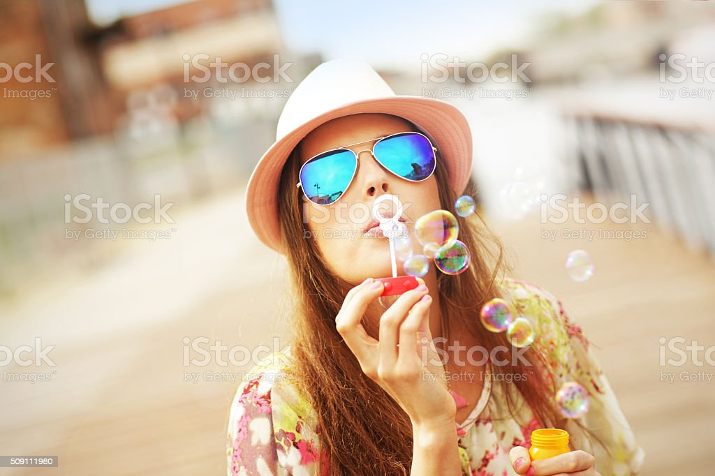Happy woman blowing soap bubbles stock photo