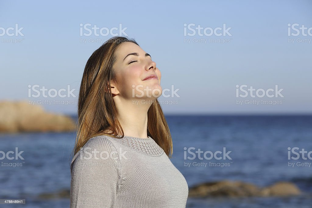 Happy woman breathing deep fresh air on the beach stock photo