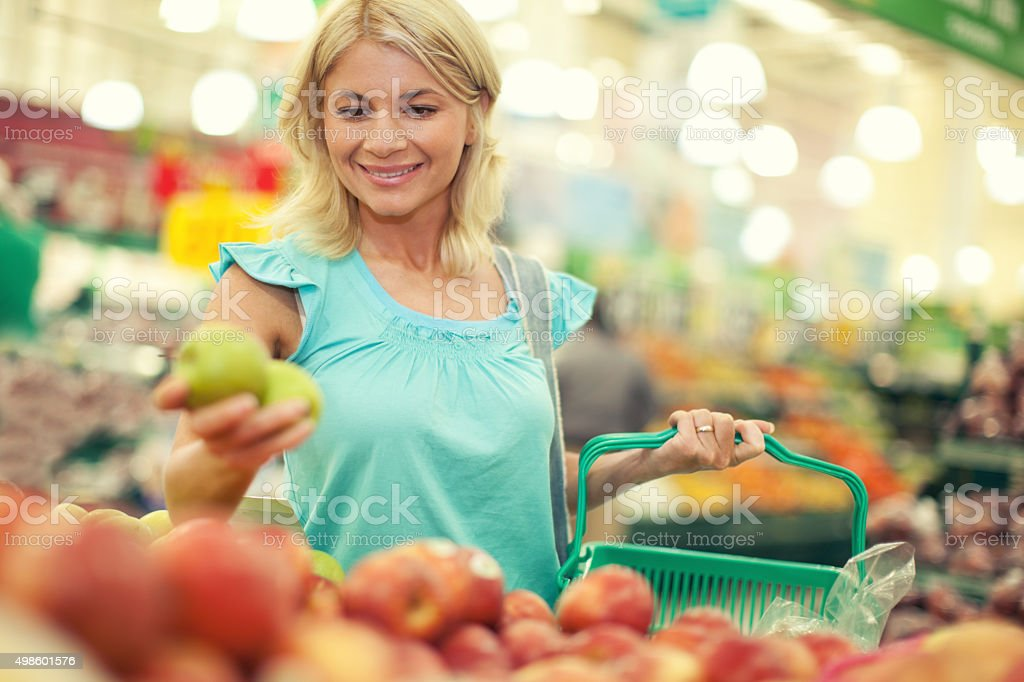 Happy woman buying fruits at farmer's market. stock photo