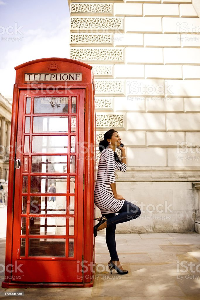 Happy Woman Calling From Traditional London Phone Booth royalty-free stock photo