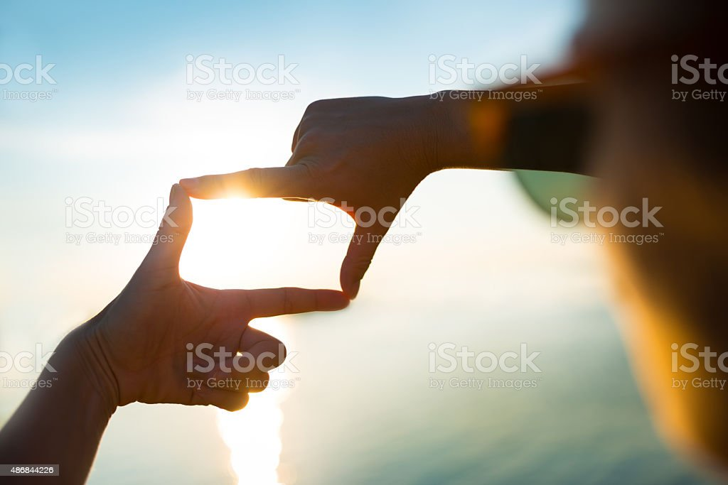 happy woman capturing the sunset by the water - Finger Frame stock photo