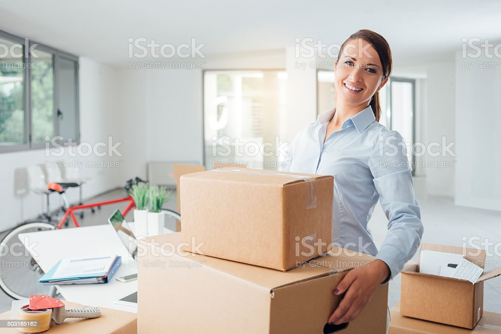 Smiling business woman carrying cardboard boxes into her new office,...