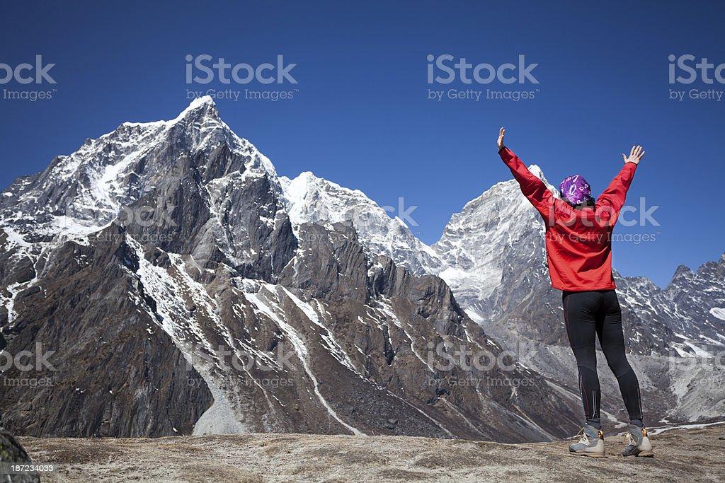 Happy woman celebrates successful climb on Himalayas royalty-free stock photo