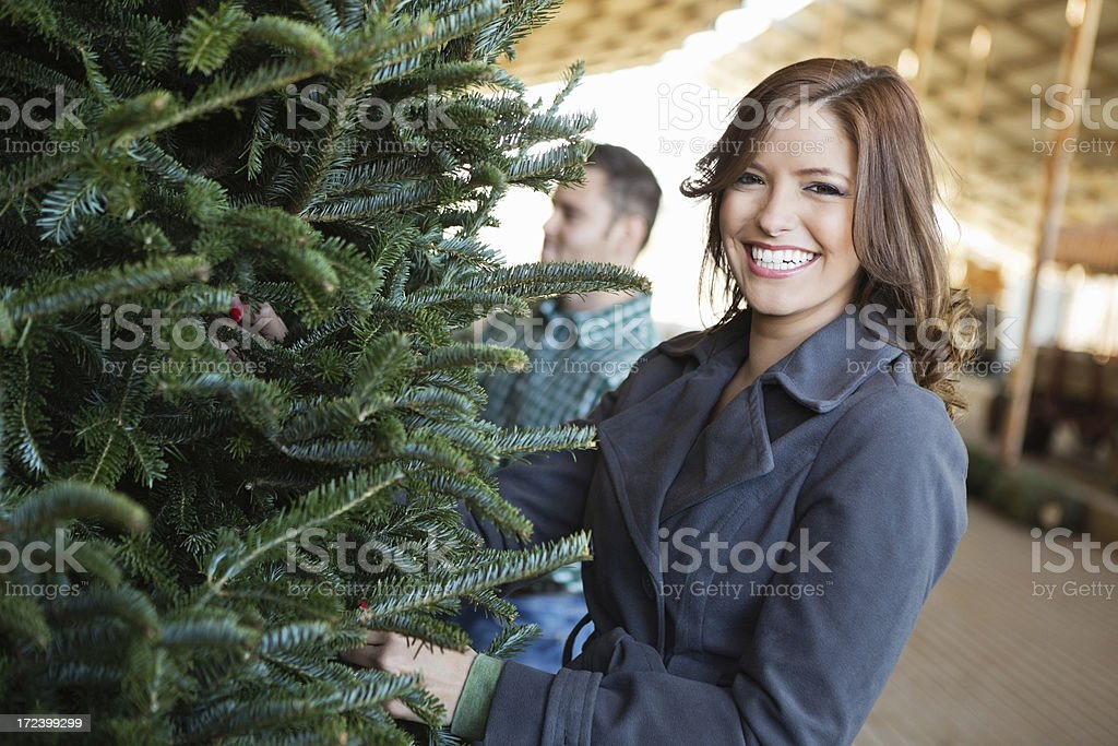 Happy woman choosing Christmas tree to purchase at farm royalty-free stock photo