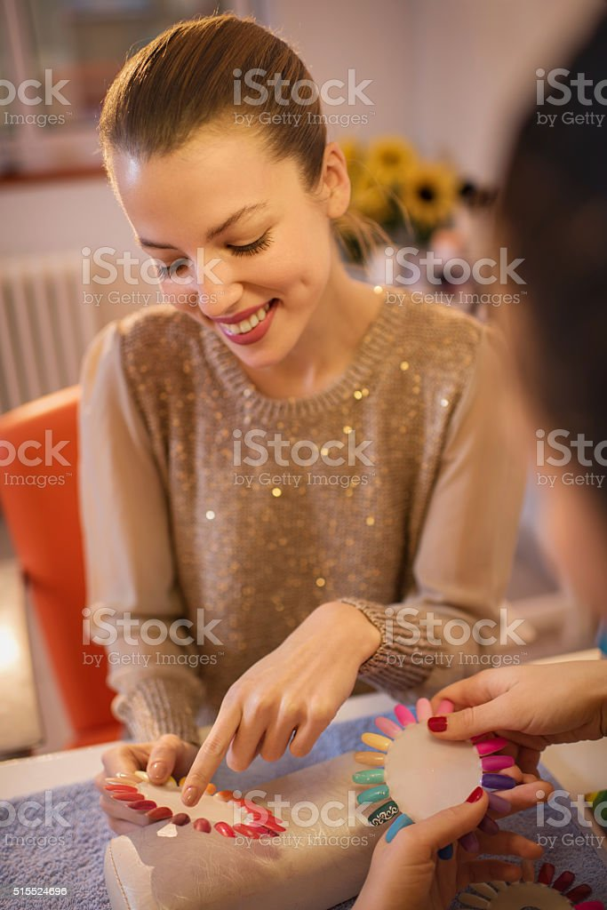 Happy woman choosing color for manicure in beauty salon. stock photo