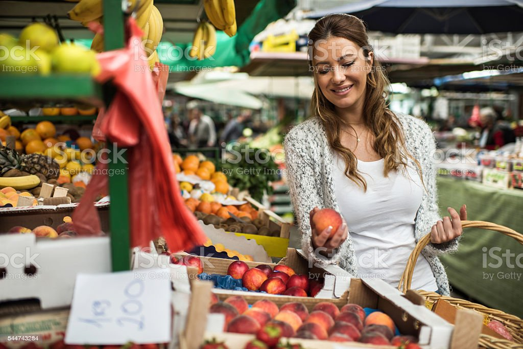 Happy woman choosing fresh peaches at farmer's market. stock photo