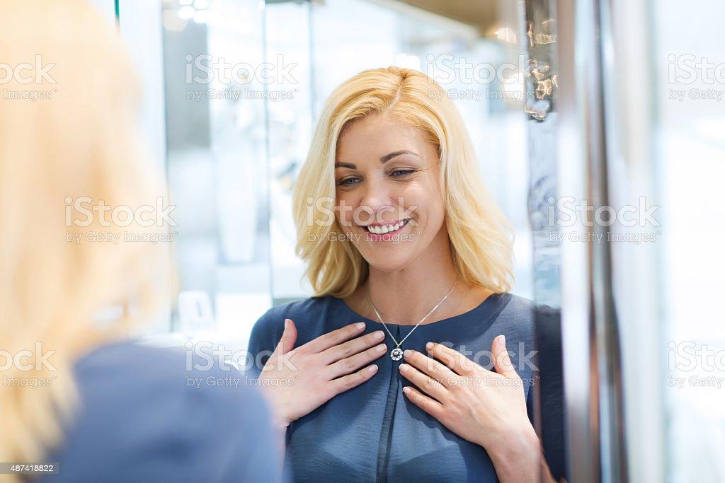 happy woman choosing pendant at jewelry store stock photo