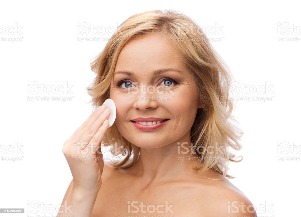 happy woman cleaning face with cotton pad stock photo