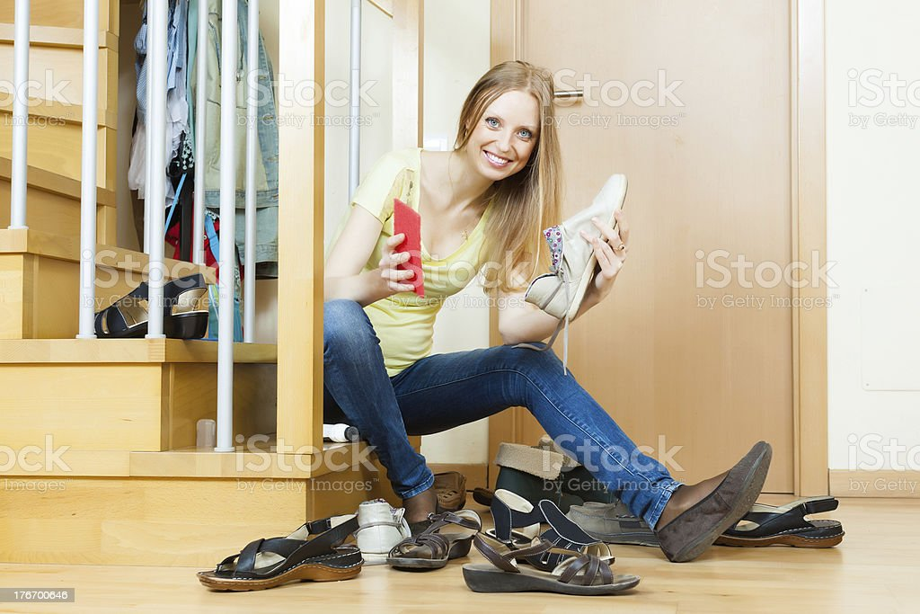Happy woman cleaning footwear royalty-free stock photo