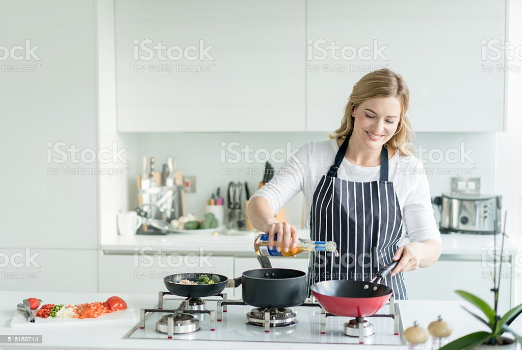Happy woman cooking at home stock photo