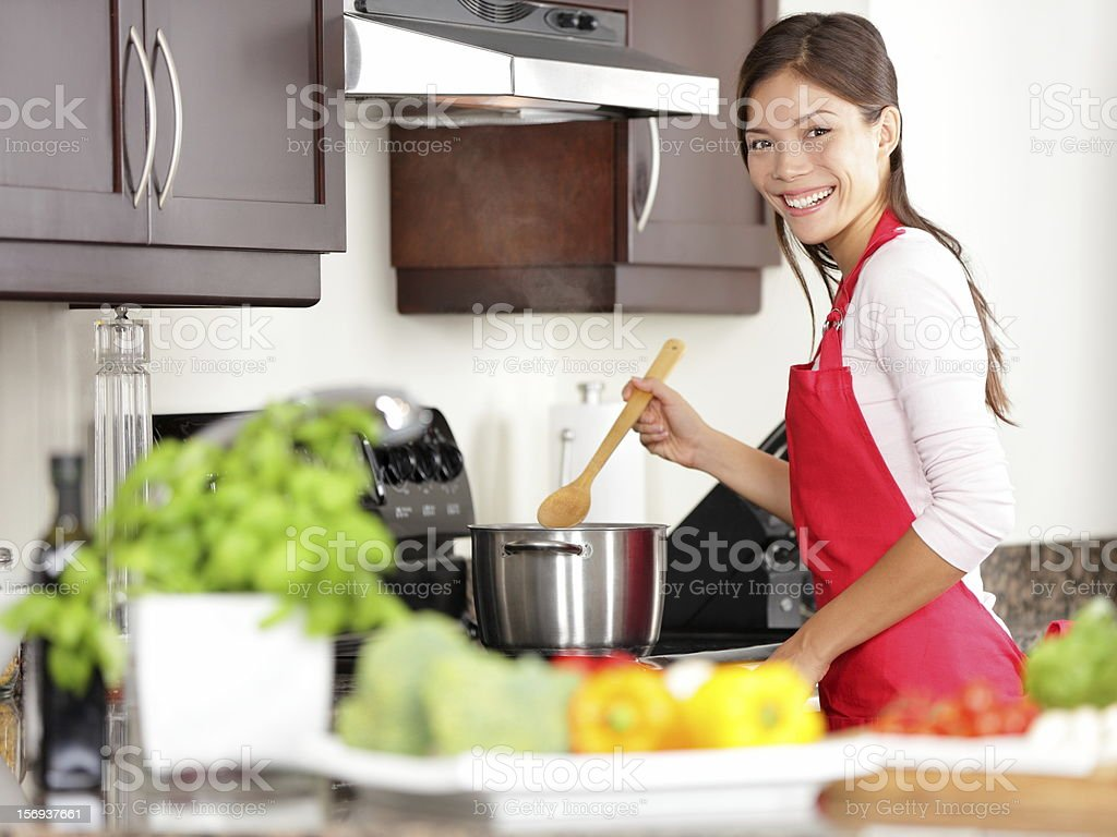 Happy woman cooking dinner in the kitchen stock photo