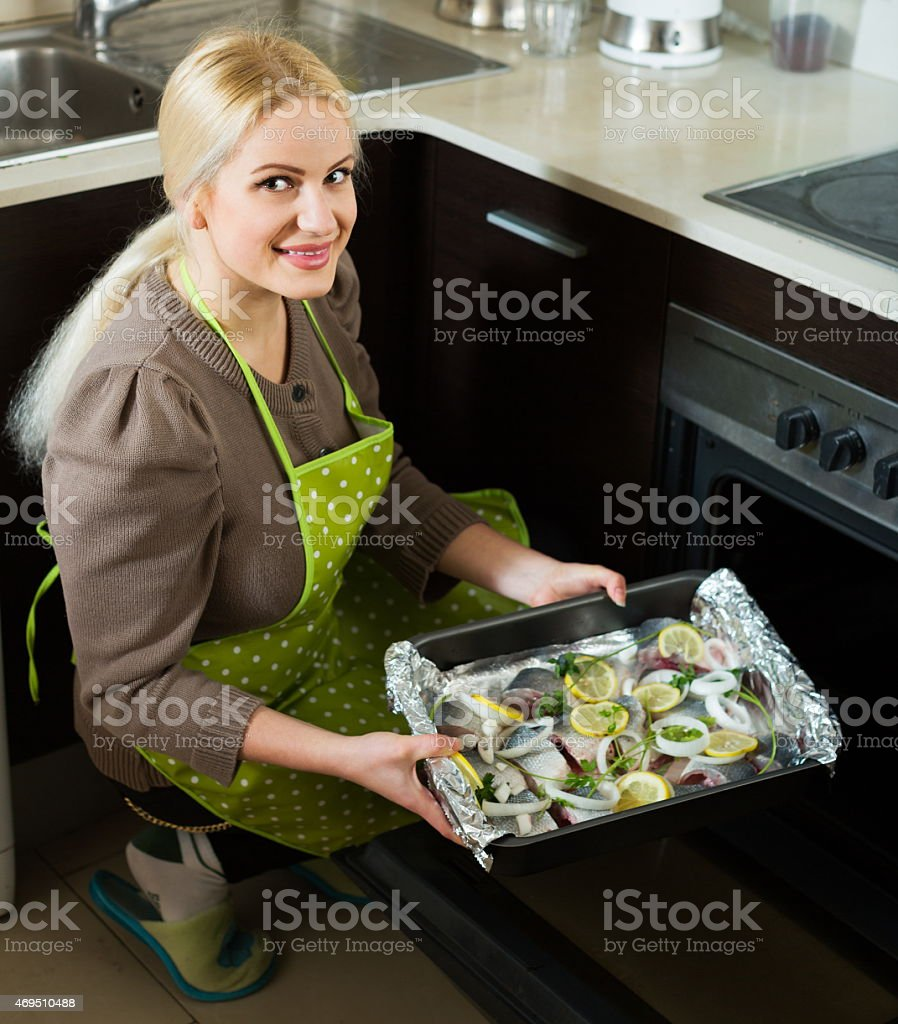 Happy woman cooking fish stock photo