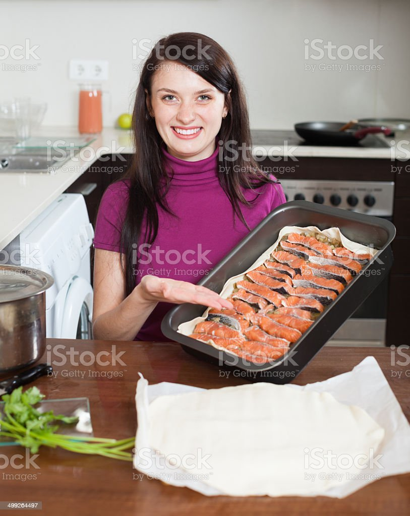 happy woman cooking fish pie in baking sheet stock photo