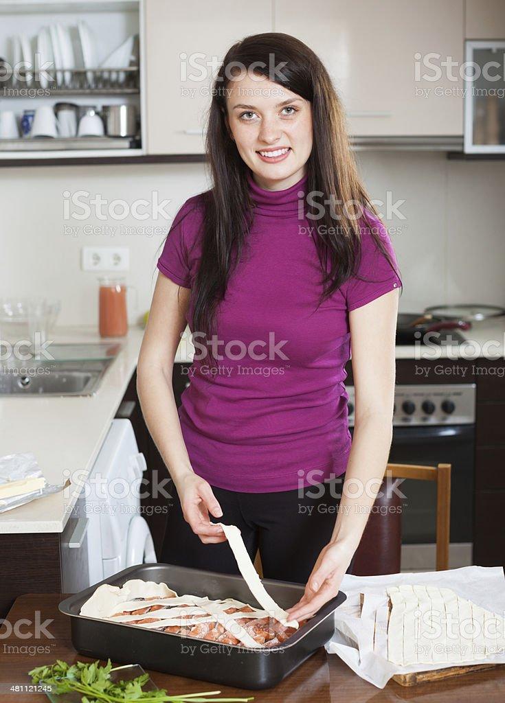 happy woman cooking fish pie stock photo