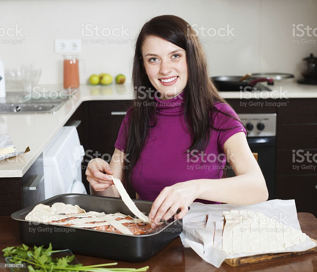 happy woman cooking fish pie with raw salmon stock photo
