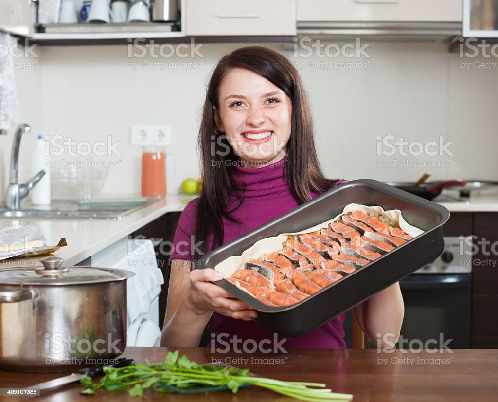 happy woman cooking fish pie with salmon stock photo