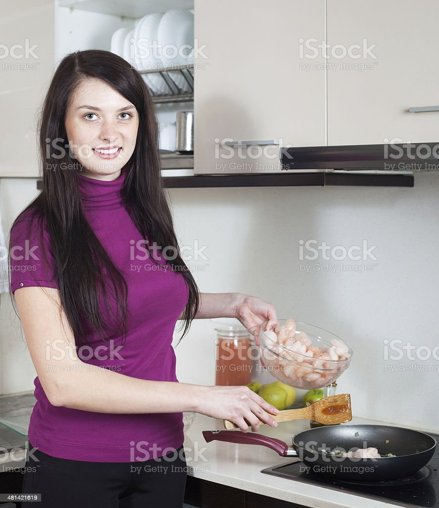 Happy woman cooking prawns in frying pan royalty-free stock photo