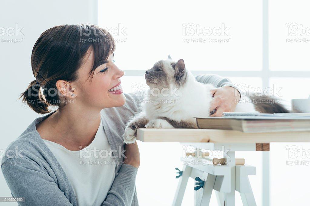 Happy woman cuddling her cat stock photo