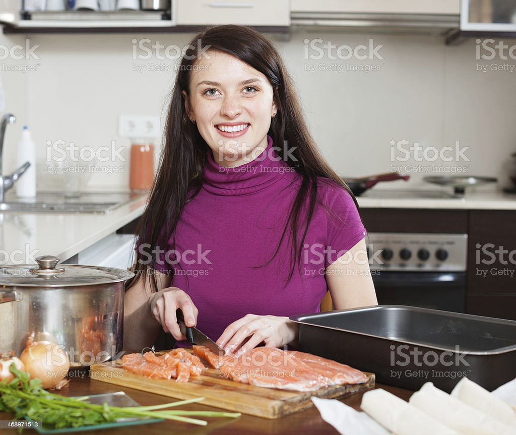 happy woman cutting salmon for fish pie stock photo