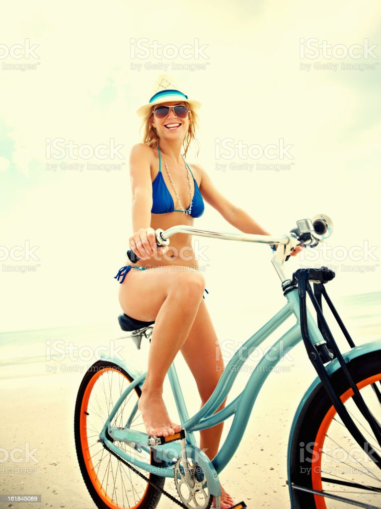 Happy woman cycling on beach royalty-free stock photo
