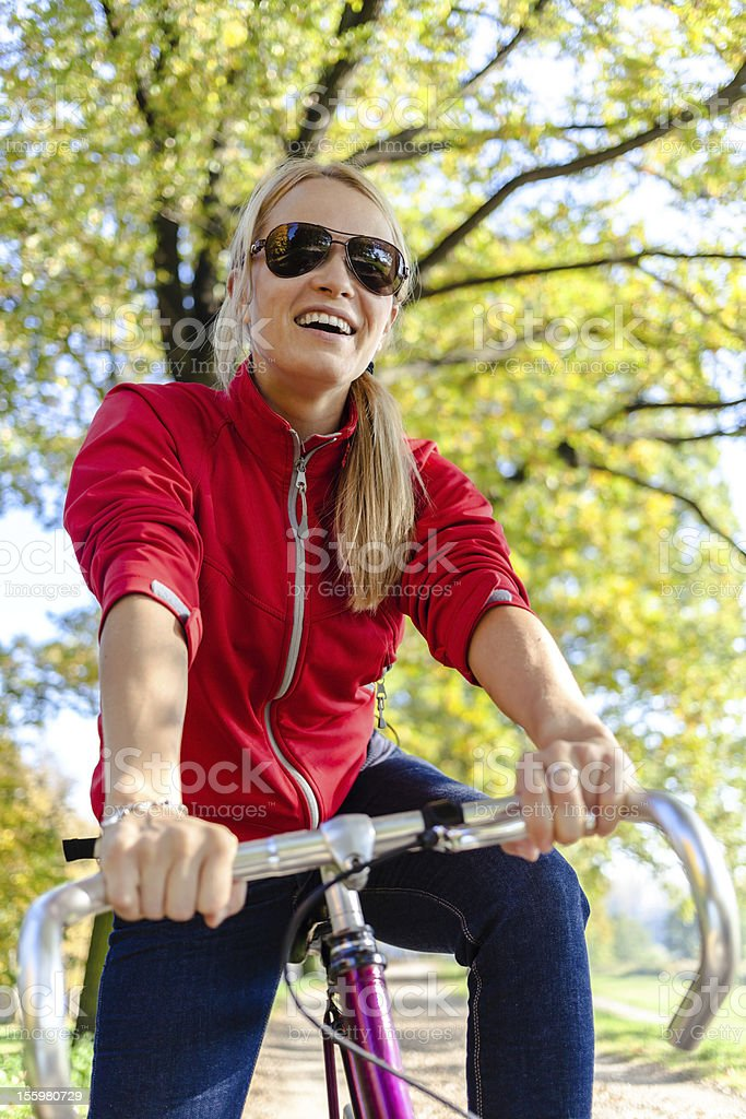 Happy woman cycling on bicycle in park royalty-free stock photo