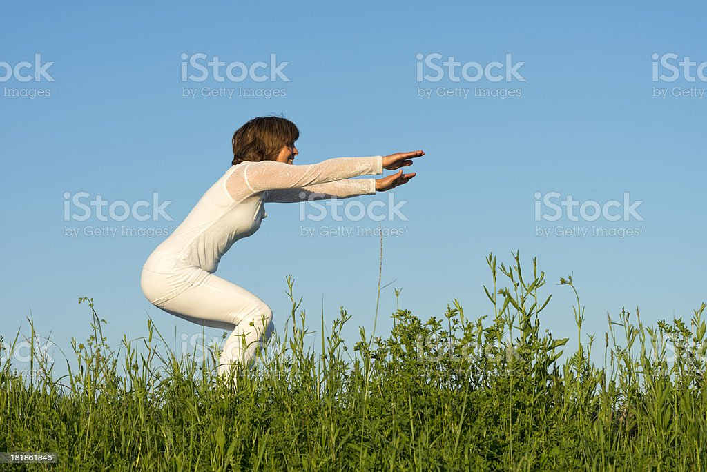 happy woman doing yoga exercises in flower meadow stock photo