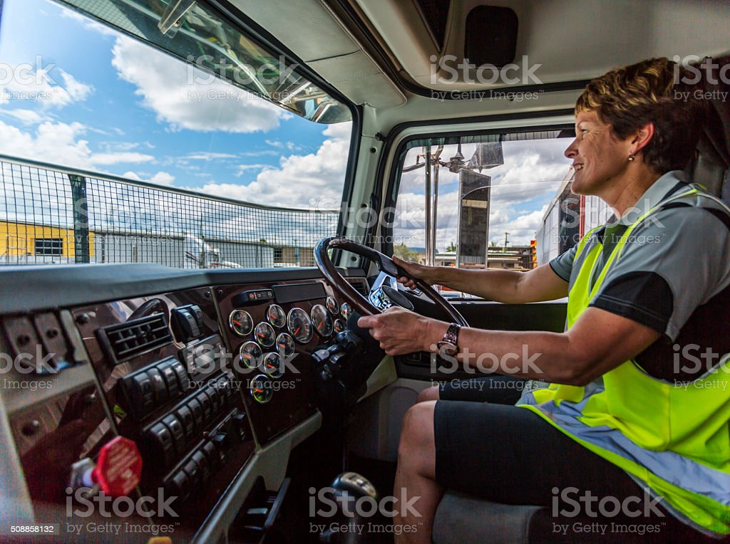 Happy Woman Driving a Truck Wearing Hi-Vis Clothes stock photo