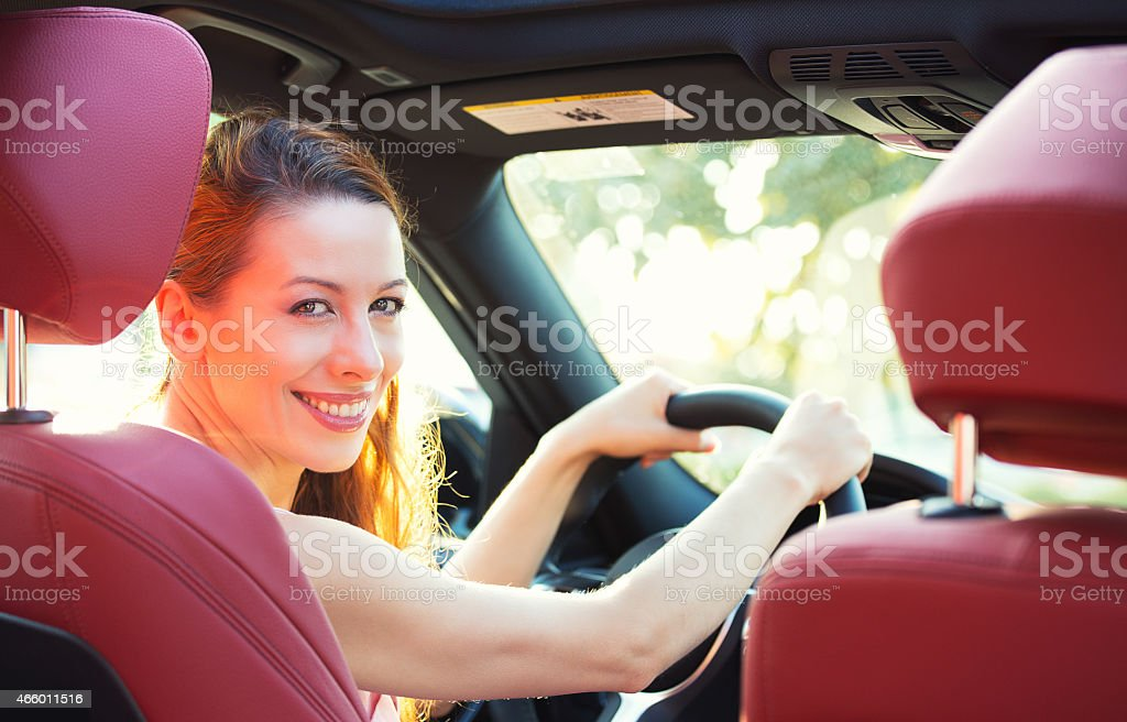 Happy woman driving her new car stock photo