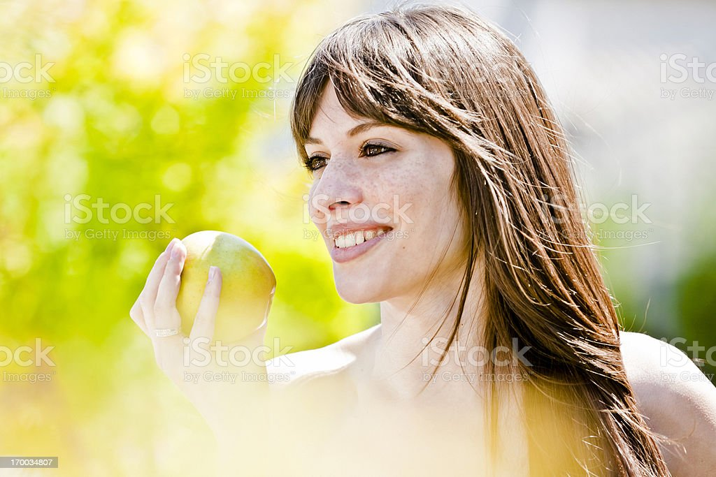 Happy woman eating apple in a Park. Healthy lifestyle. royalty-free stock photo