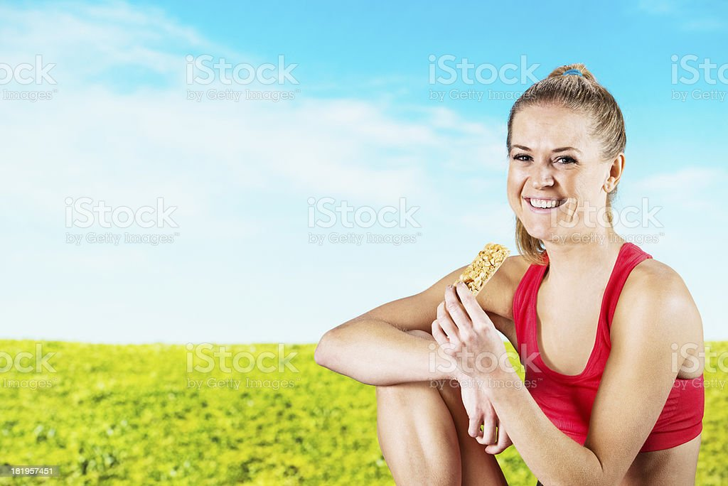 Happy woman eating cereal bar in a field royalty-free stock photo
