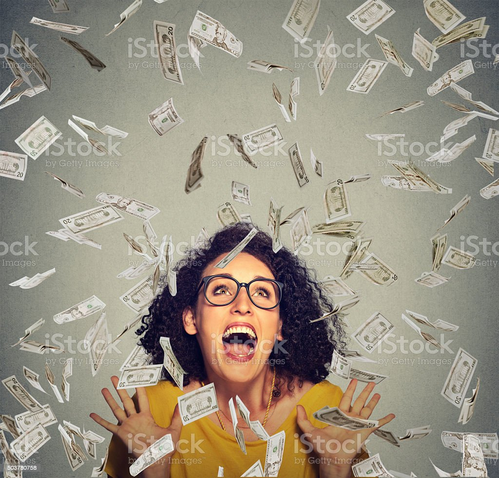 happy woman ecstatic celebrates success under money rain stock photo