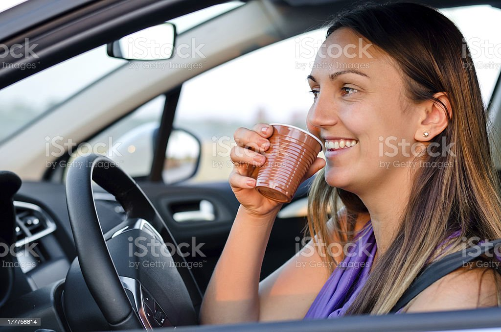 Happy woman enjoying a drink while traveling stock photo