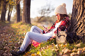 Happy woman enjoying  autumn and using smart phone